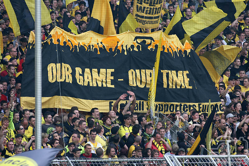 Picture of supporters with Our Game - Our Time Banner